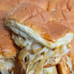These Cheesy French Onion Chicken Sandwiches are the ultimate party or game day food! Soft rolls loaded up with slow cooker chicken, caramelized onions and loads of melt cheese. This is the perfect recipe to feed your hungry crowd!