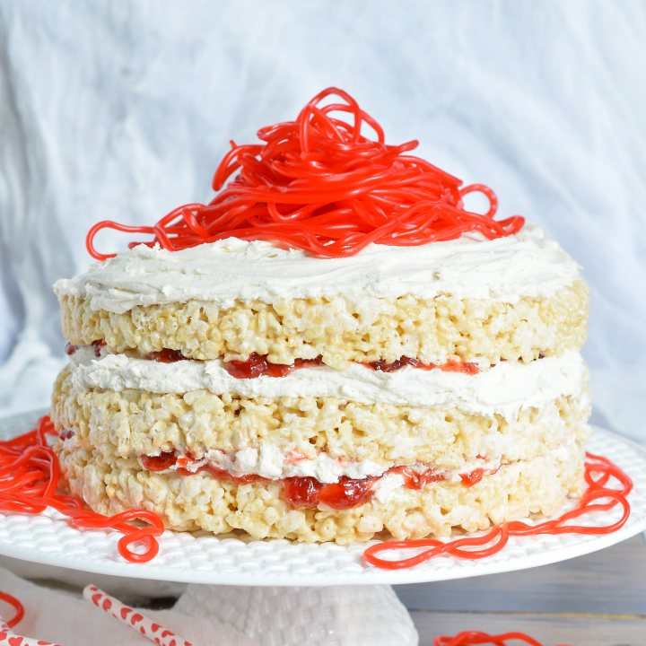 This Rice Crispy Treat Candy Cake is a fun and whimsical dessert recipe. Perfect for Valentine's Day, kids birthdays or for anyone that doesn't like traditional cake. Three layers of rice crispy treats smeared with vanilla butter cream, strawberry jam then topped with strawberry licorice ropes!