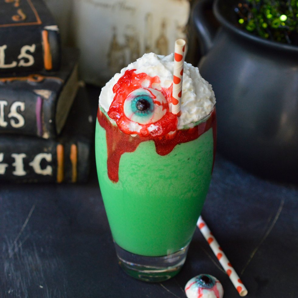 Make this Eye of ToadHalloween Milkshake Recipe for all of your creepy little monsters! This Halloween dessert is made with cookies and cream ice cream, green coloring, whipped cream, red blood gel and topped with a gummy eyeball. This fun recipe is kid approved!