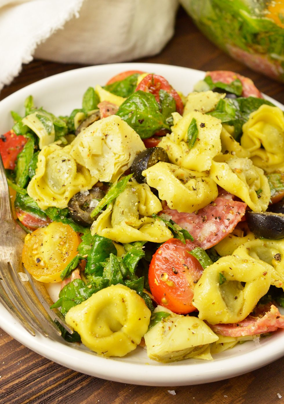 Prepare to be obsessed! This Spinach Tortellini Italian Pasta Salad Recipe is bursting with color, flavor and is nutritious. A perfect blend of fresh spinach, tomatoes, olives, artichokes, salami and tortellini tossed with an Italian dressing. This side dish can be served hot or cold and be prepared ahead of time. #pasta