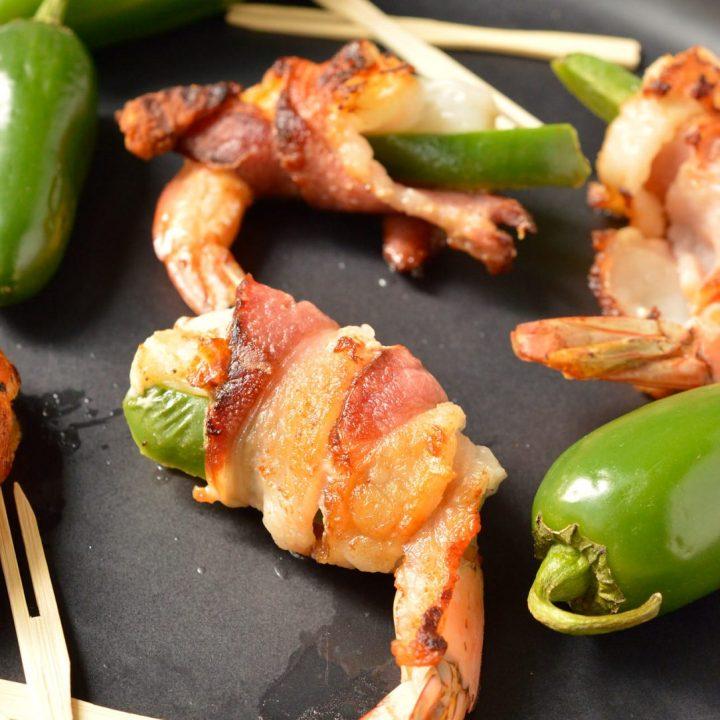 close up of bacon wrapped shrimp next to jalapeños