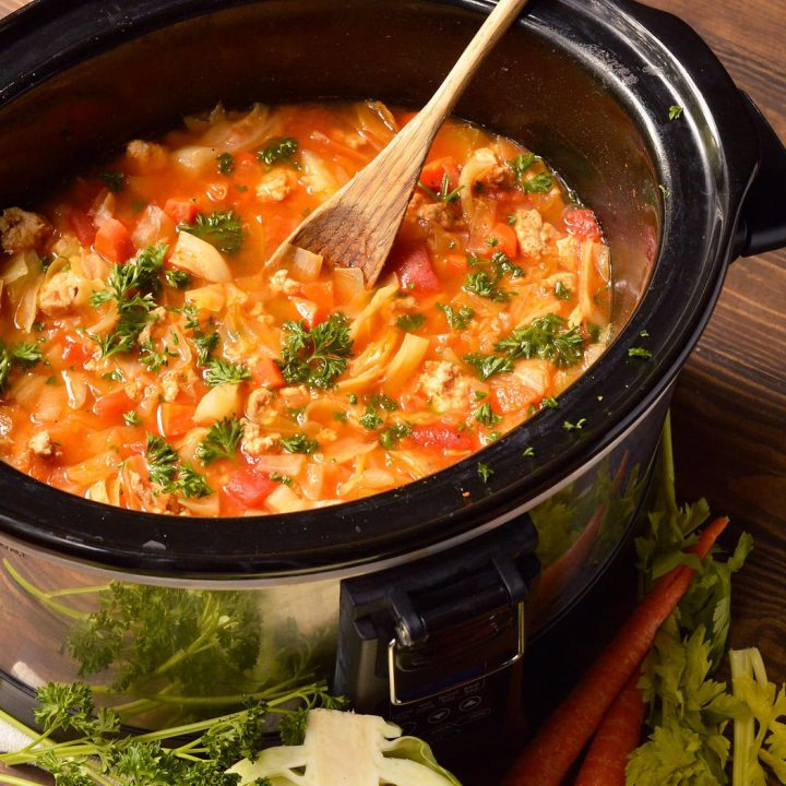 cabbage roll soup in slow cooker with wooden spoon