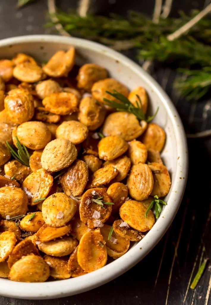 close up photo of freshly toasted golden brown marcona almonds with fresh green rosemary