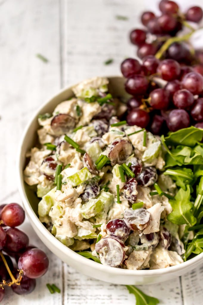 chicken salad with grapes in a white bowl along with fresh green arugula salad and a bunch of purple grapes