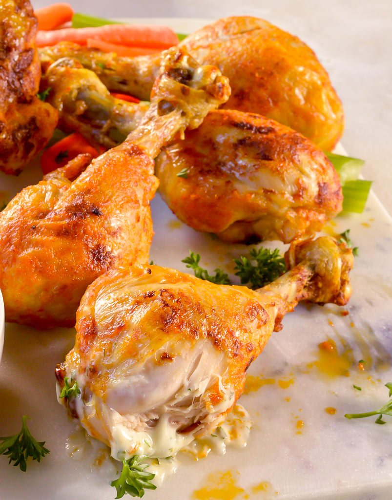 close up of chicken drumstick with bite taken out of it, showing juicy meat inside