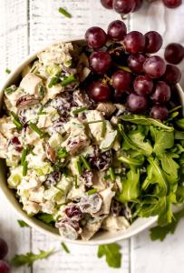 chicken salad with red grapes and green leafies in white bowl