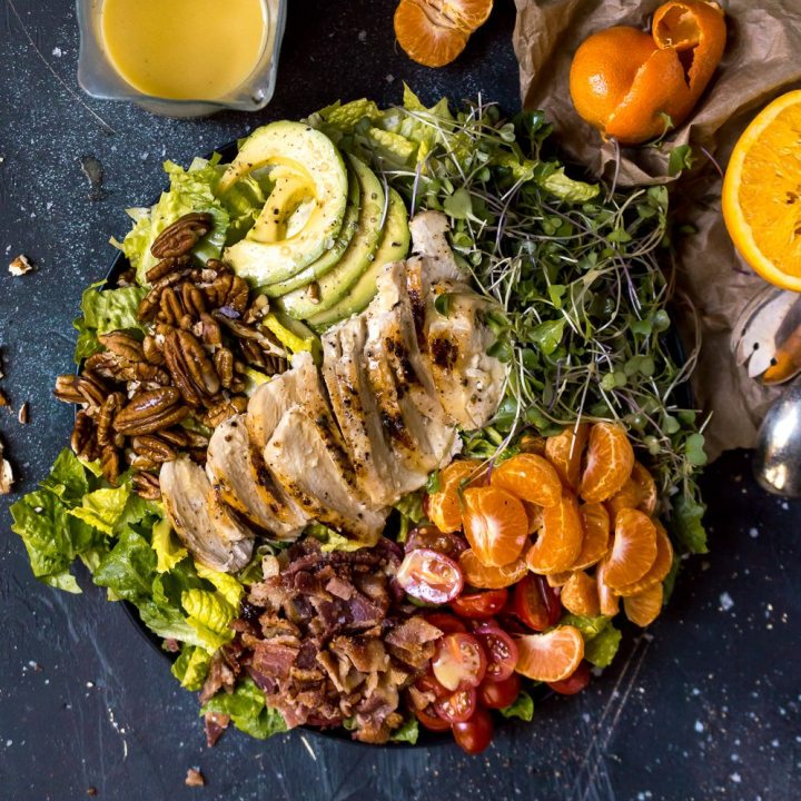 salad filled with chicken, oranges, bacon, pecans and avocado