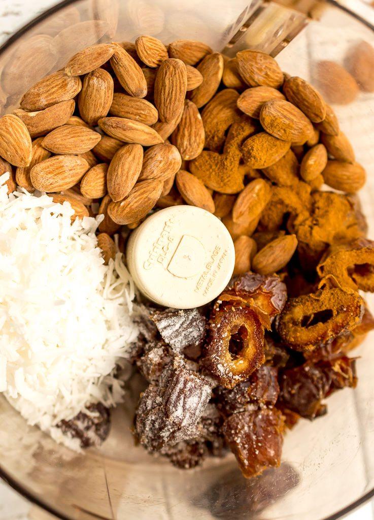 close up photo of food processor with almonds, dates, coconut, cinnamon and sea salt