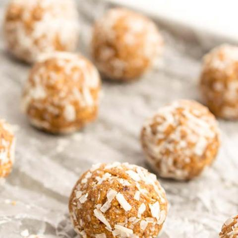 round energy balls with coconut flakes on wax paper