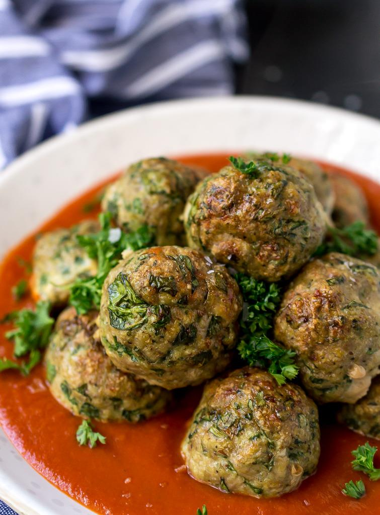 browned meatballs with bright green flecks of spinach inside, surrounded by fresh green parsley and red marinara sauce in a white bowl