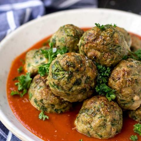 baked turkey meatballs with spinach in white bowl with red sauce