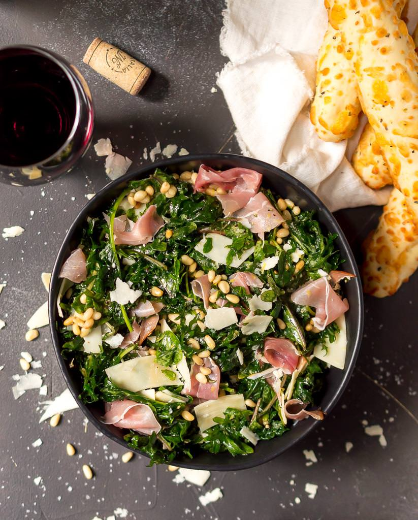 overhead photo of kale salad recipe with prosciutto and parmesan. red wine, cork and breadsticks on the side
