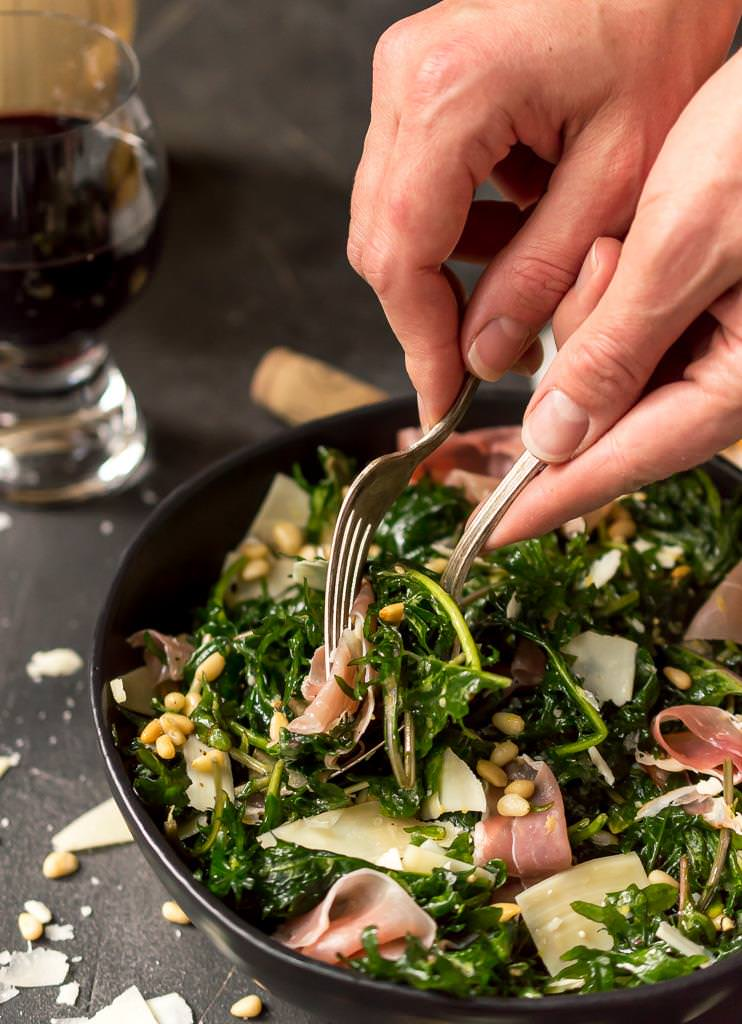 kale salad being served with a fork and spoon