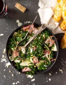 deep green kale salad topped with pine nuts, prosciutto, parmesan cheese. breadsticks and a glass of red wine on the side