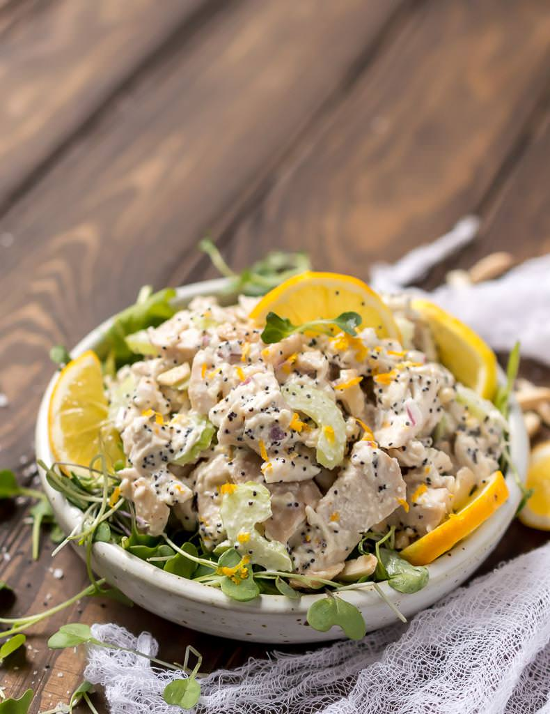 full view of white bowl filled with poppy seed lemon chicken salad. white cheesecloth on the side