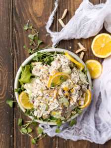 overhead photo of white bowl with chicken salad. lemons and micro greens around the bowl
