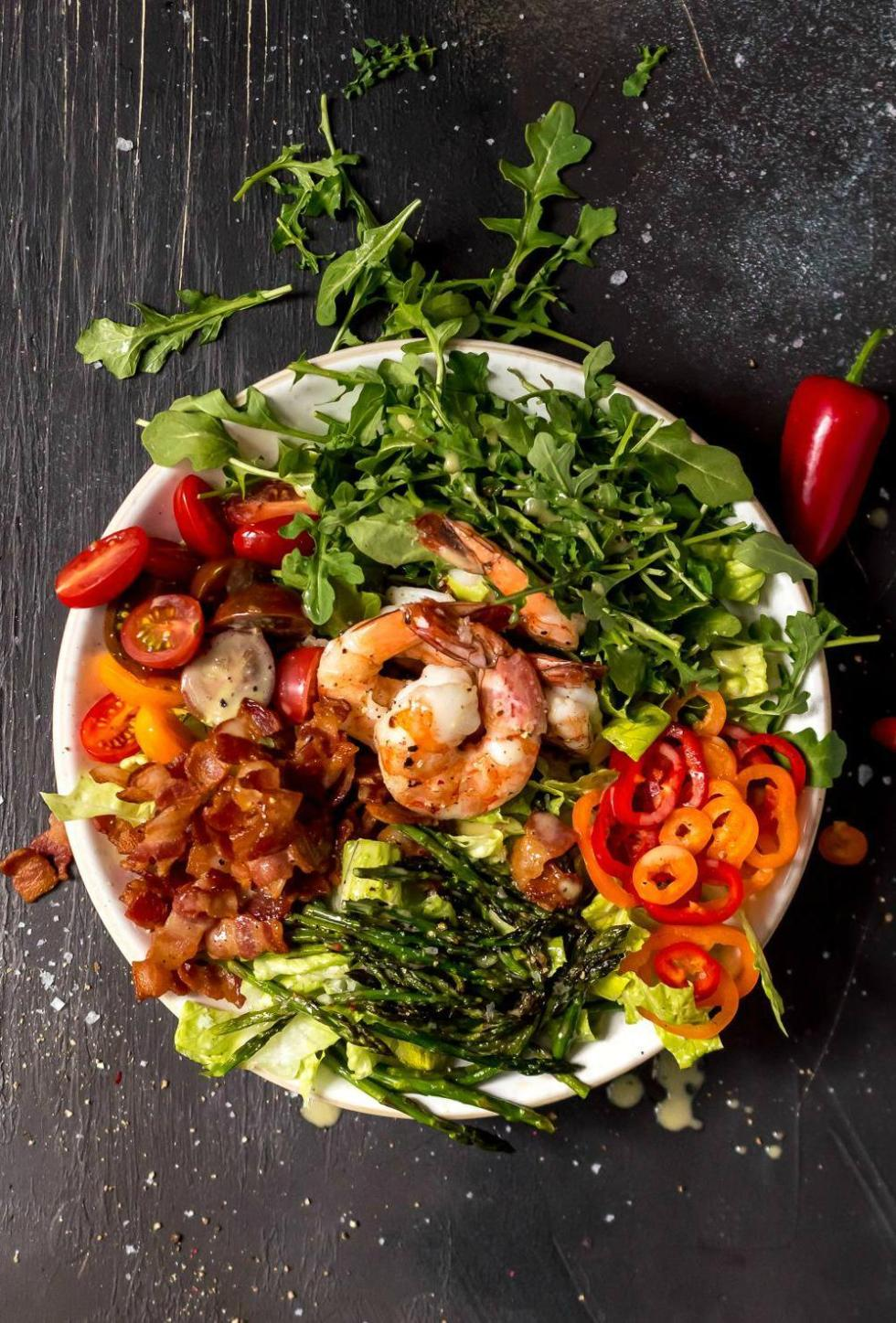 overhead photo of a messy salad topped with roasted asparagus shrimp bacon tomatoes mini peppers and lemon pepper dressing, white bowl black background
