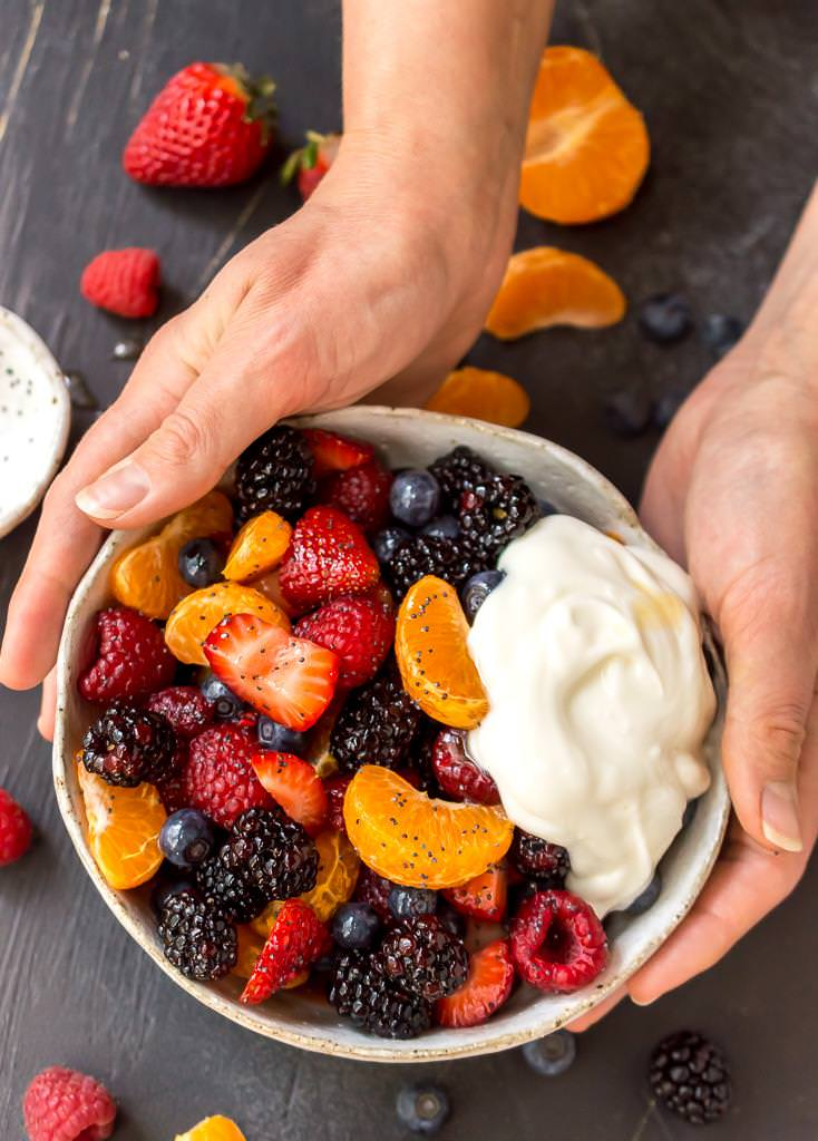 hands holding a white bowl filled with berry fruit salad topped with a dollop of white yogurt