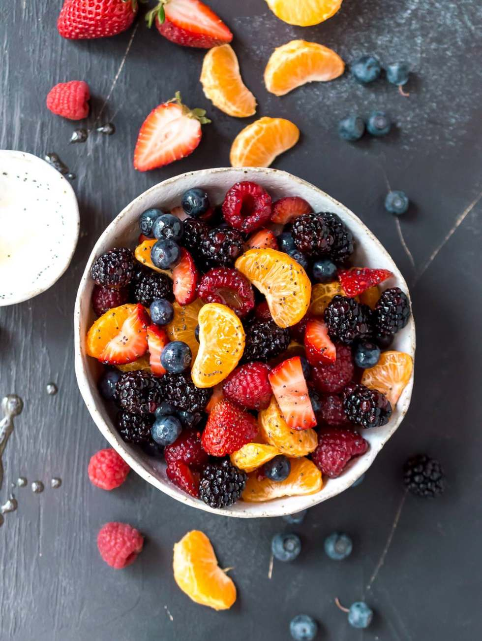 over head photo of berry fruit salad with berries and orange segments on black background