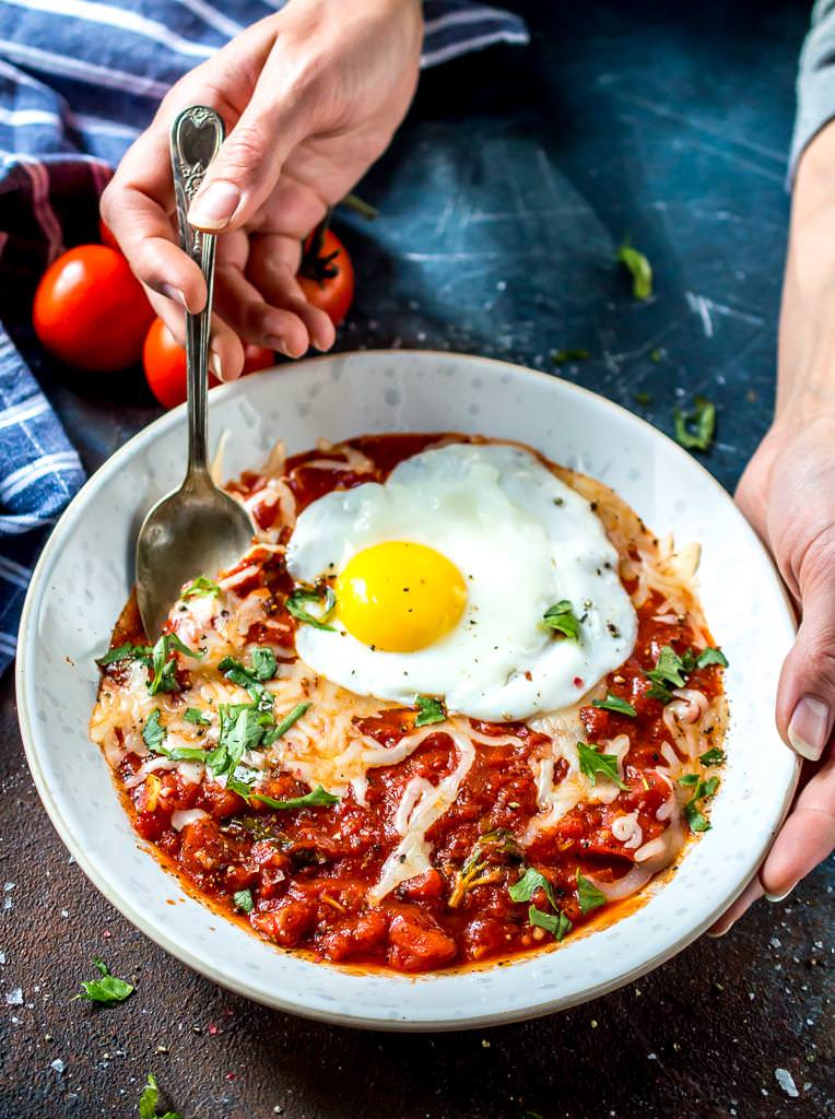 hands holding a white bowl filled with bright red tomato sauce topped with a fried egg