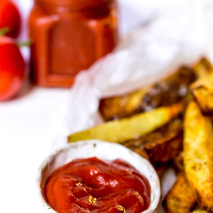 bright red ketchup in small white bowl next to oven fries
