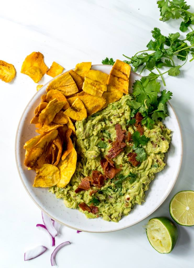 over head photo of bacon guac recipe mixed together in a white bowl with plantain chips on the side