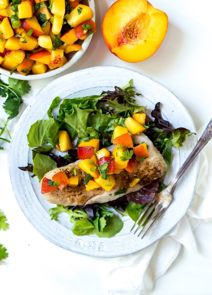 overhead photo of rock fish on top of green salad with peach salsa on top