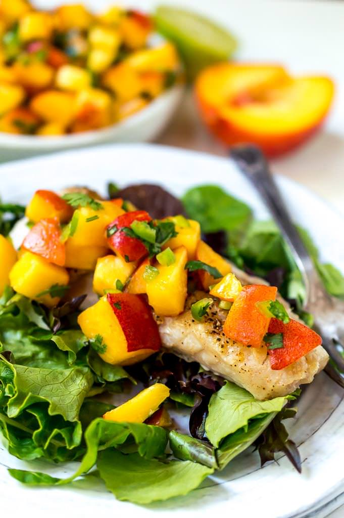 close up photo of rock fish topped with peach salsa