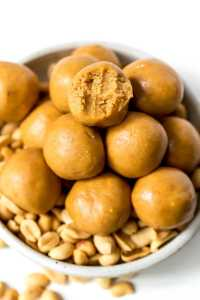 close up photo of peanut butter protein balls, one has a bite taken out
