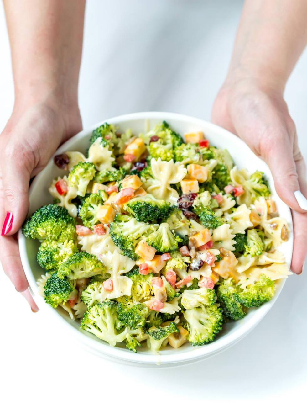 hands holding a white bowl filled with broccoli salad recipe