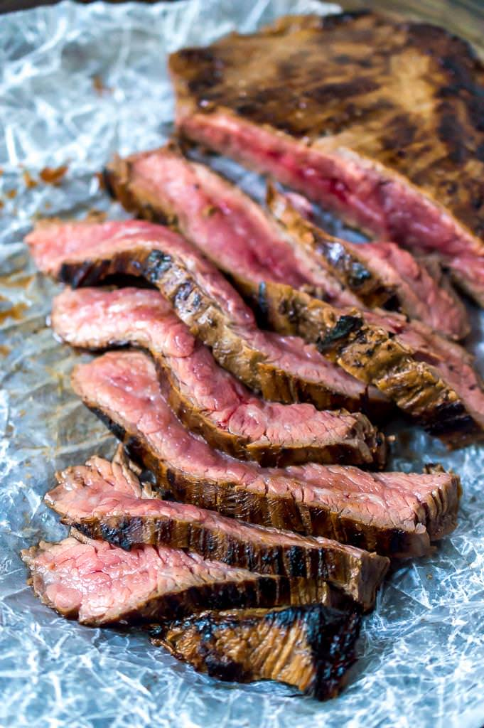 close up photo of sliced flank steak recipe with a slightly charred crust and red-pink in the middle