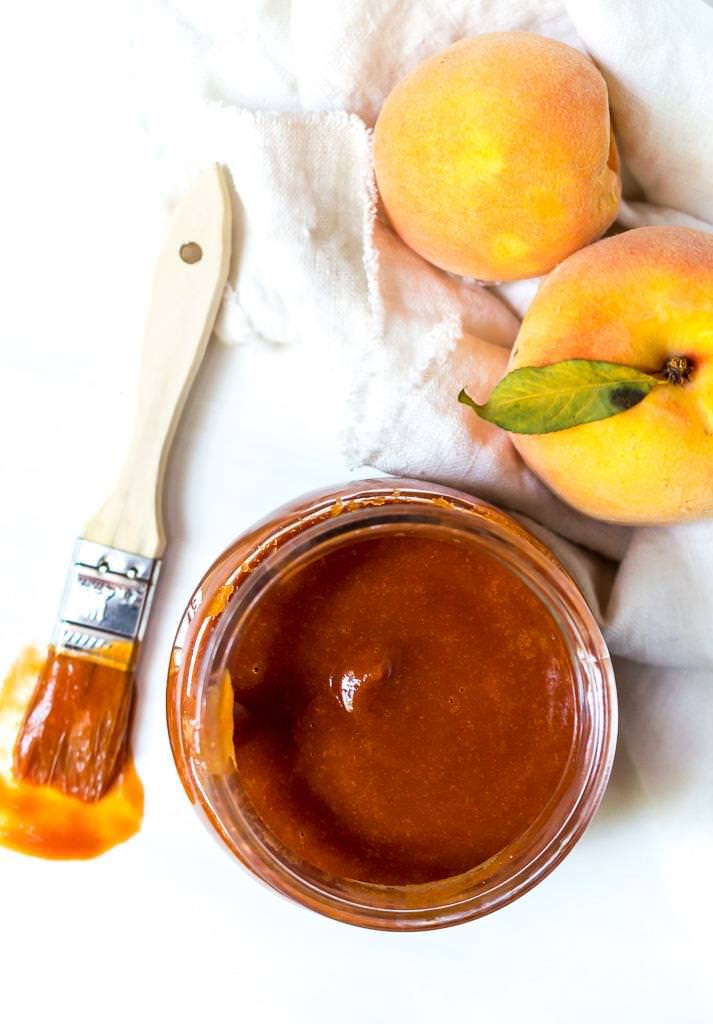 over head photo of peach barbecue sauce recipe with bbq brush and fresh peaches on the side