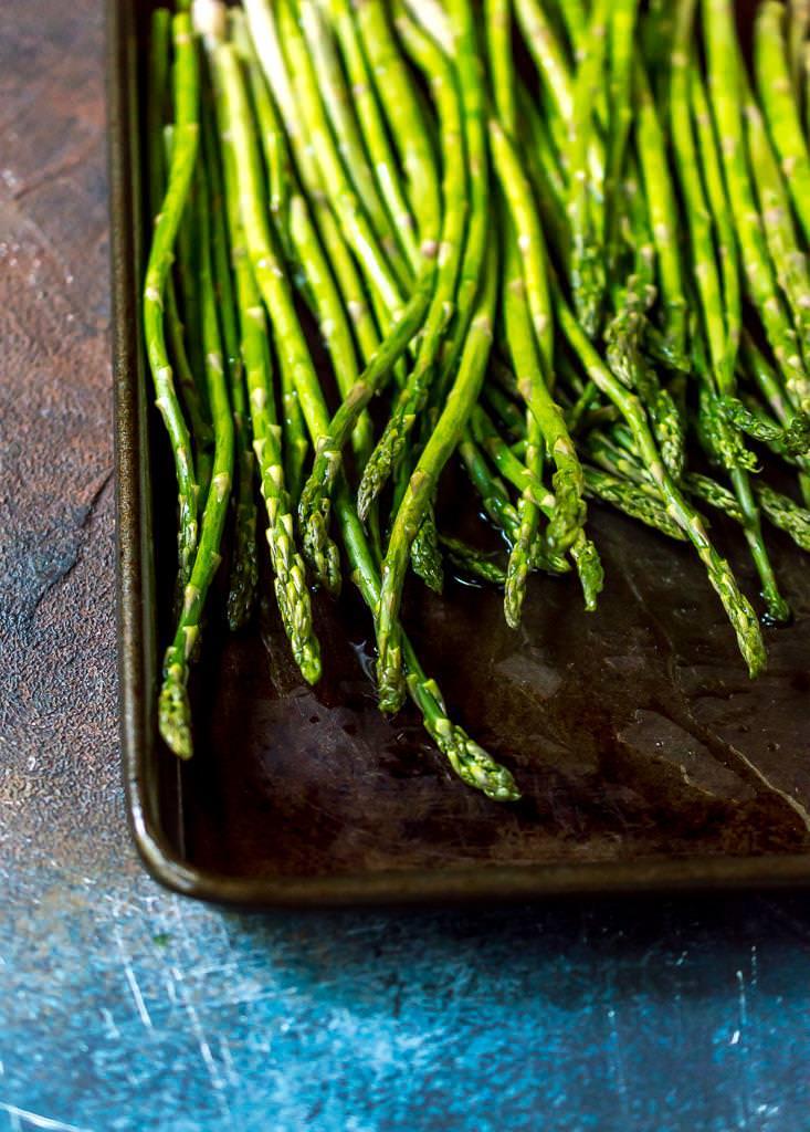 fresh asparagus on rimmed baking sheet prepped for oven roasted asparagus recipe