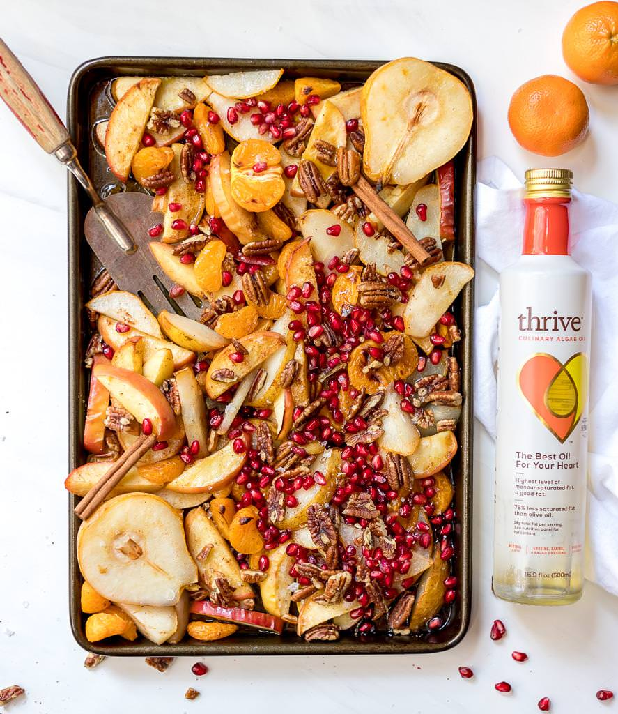 baking sheet with baked apples, pears and mandarins with a bottle of thrive oil on the side