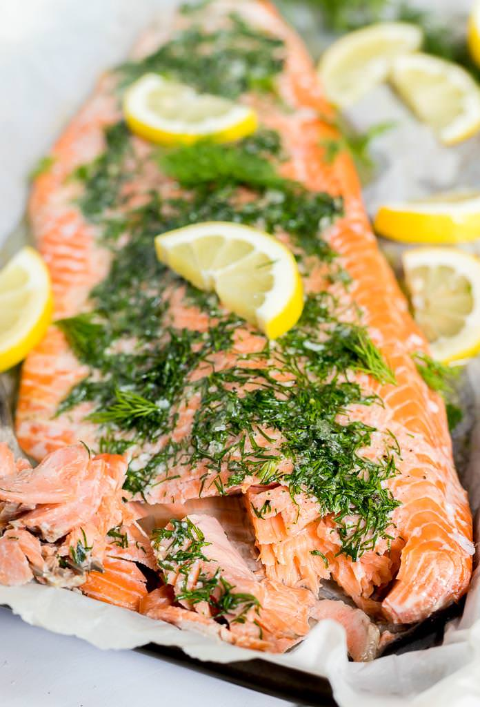 oven baked salmon covered in fresh green dill and bright yellow lemons