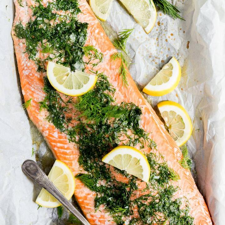 fresh out of the oven, baked salmon topped with fresh dill and lemons