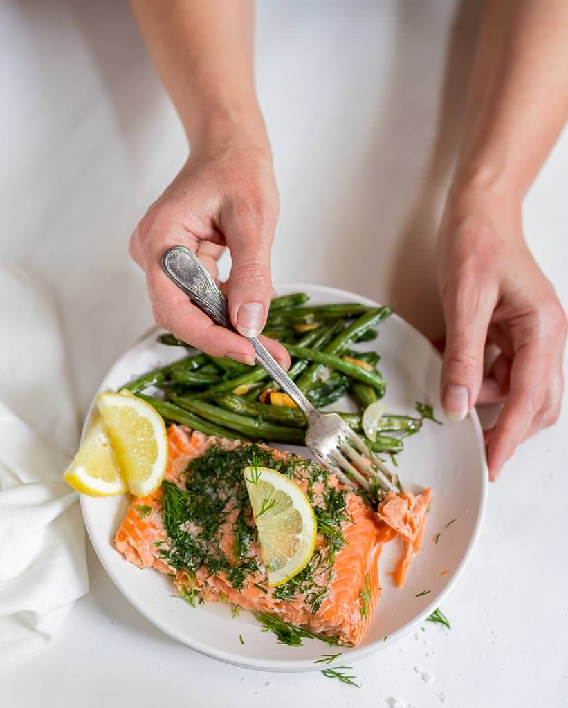 white plate with fresh baked salmon, green beans and lemons