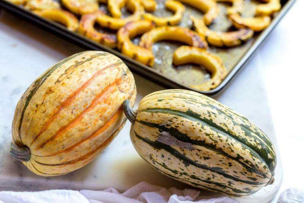 two whole delicata squash before being sliced and roasted