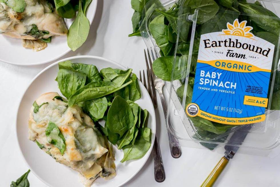 plated smothered chicken with package of Earthbound Farm Baby Spinach on the side