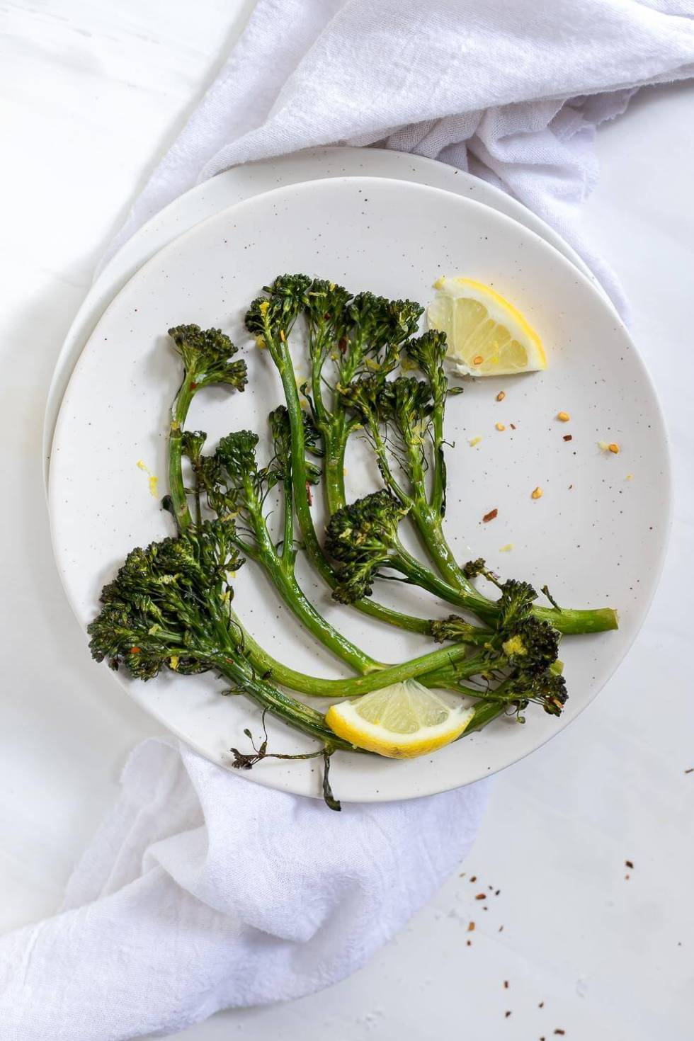 white plate with fresh green roasted broccolini and lemons