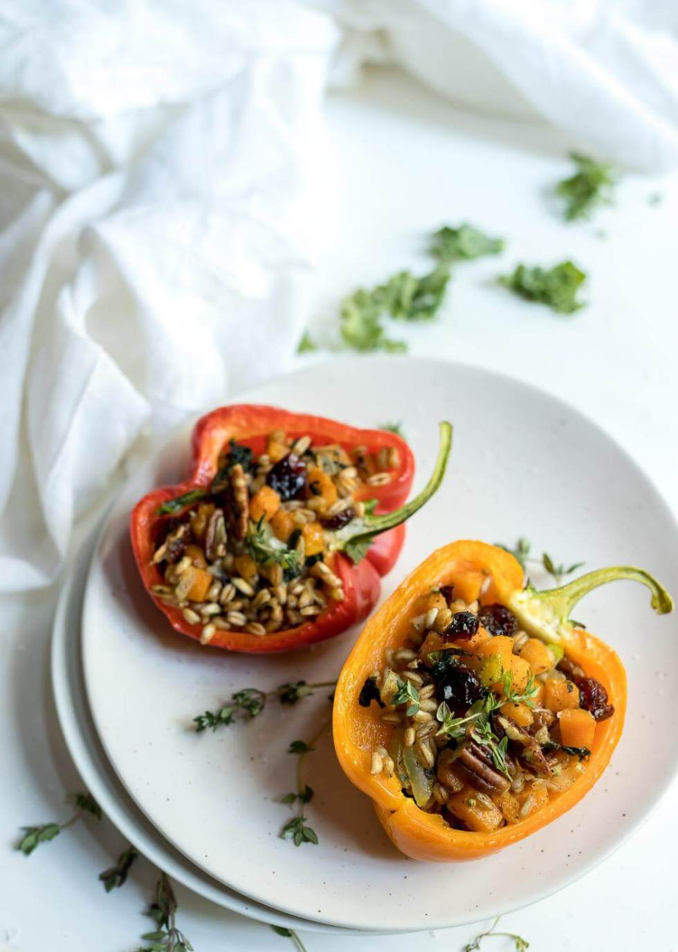 farro salad stuffed peppers recipe on white plates with white background
