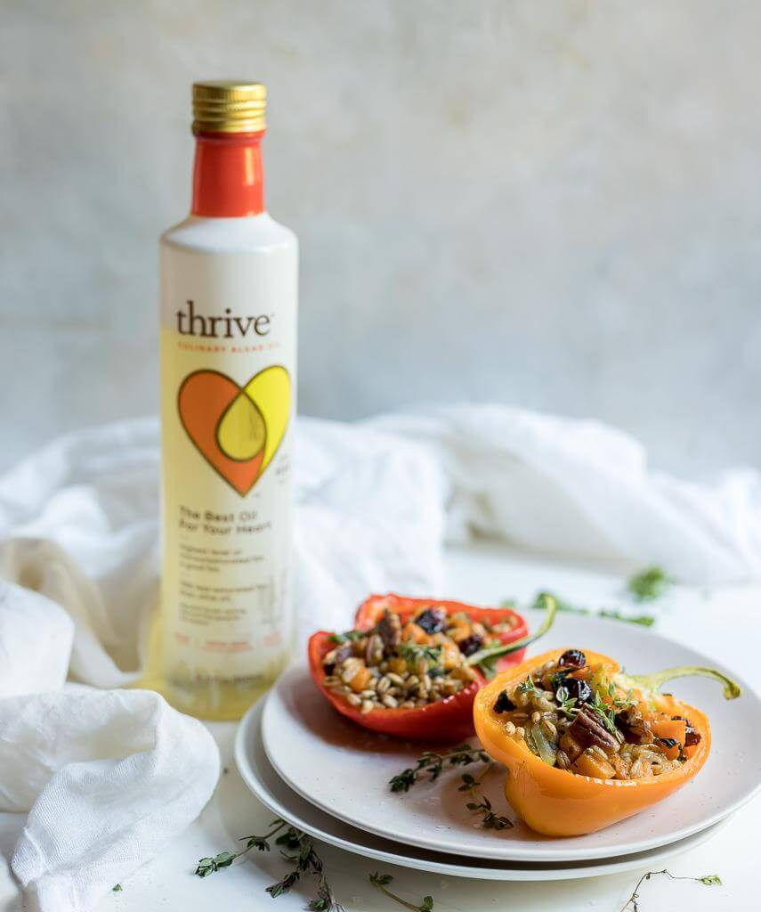 farro salad stuffed peppers on white plate with bottle of Thrive Culinary Algae Oil in background