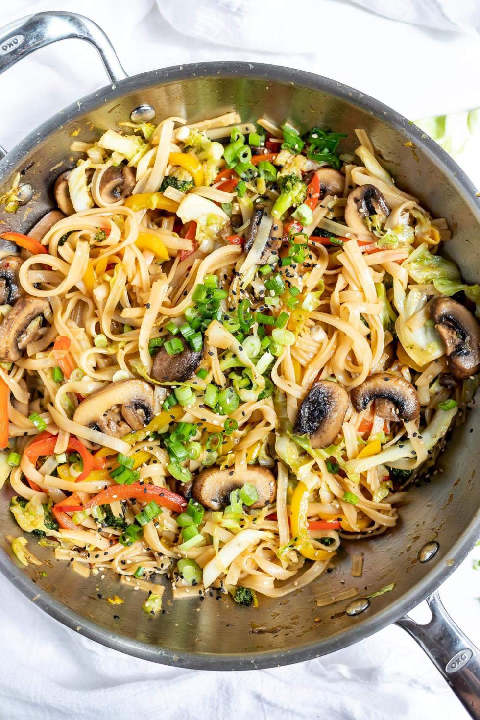 stir fry vegetables and chinese noodles in large silver wok
