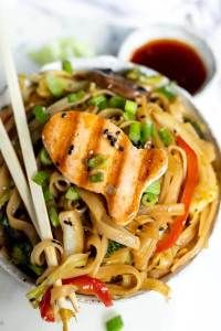 large bowl of vegetables and chinese noodles topped with a fish shaped grilled salmon patty