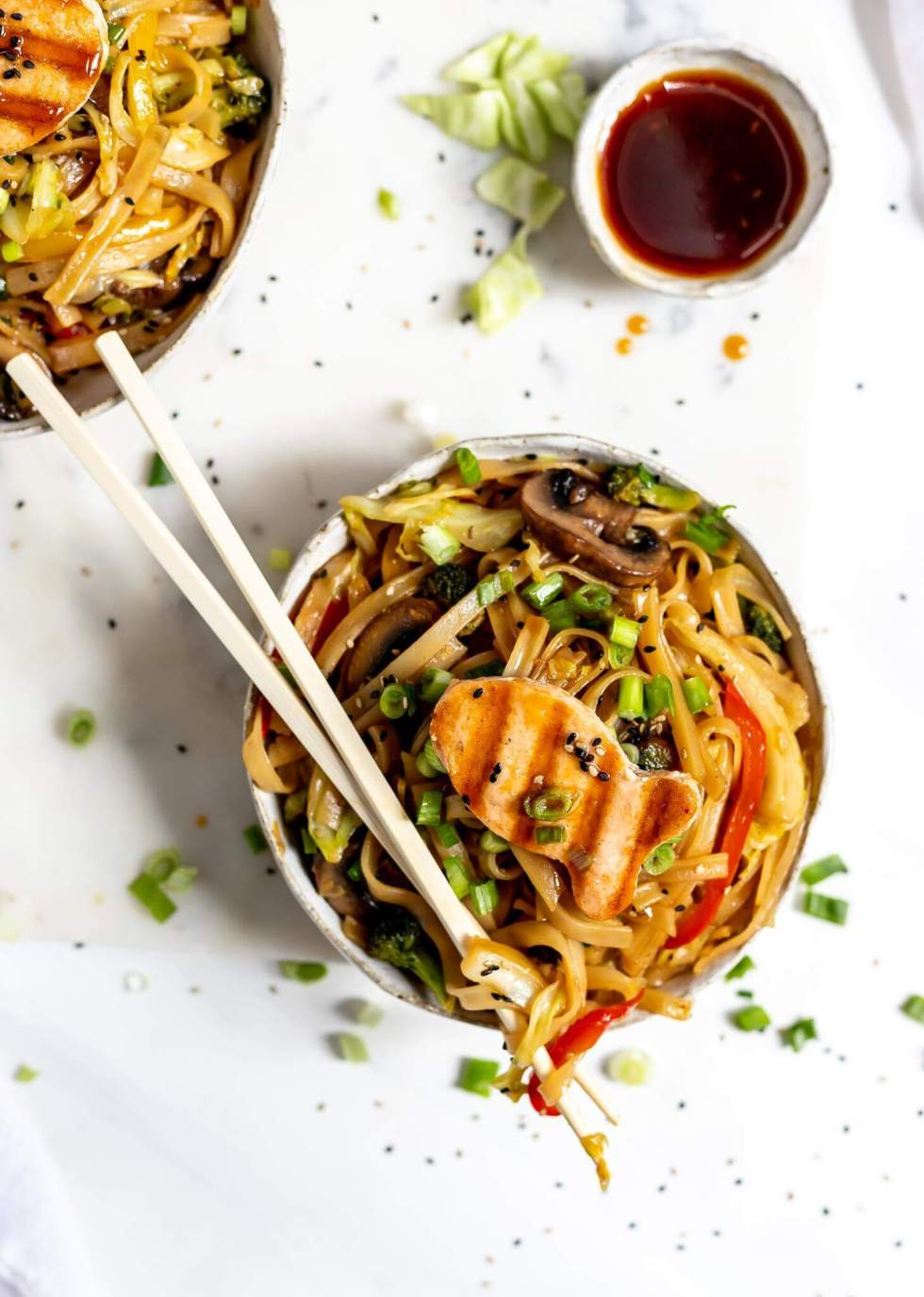 bowl of chines noodles with chopsticks on top and a small bowl of sauce on the side
