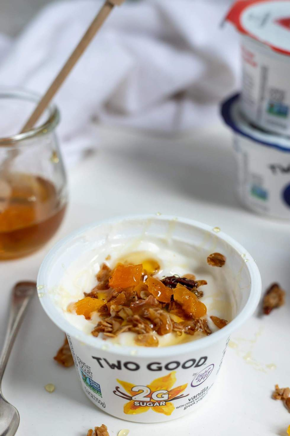 two good yogurt cup topped with homemade granola and honey