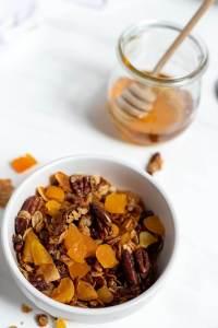 homemade granola in white bowl next to jar of honey