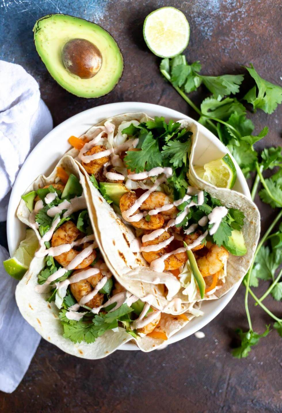 two loaded shrimp tacos with cilantro, lime and avocado on the side