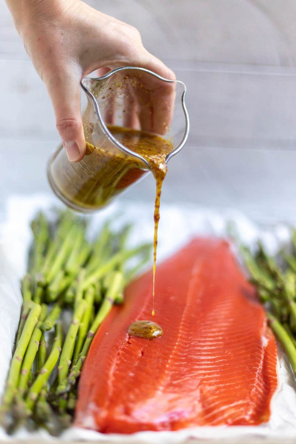 maple mustard sauce being drizzled over salmon and asparagus
