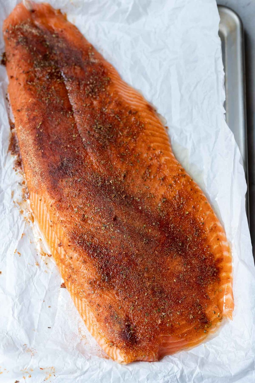 blackened salmon rubbed with spices and laying on parchment paper before baking